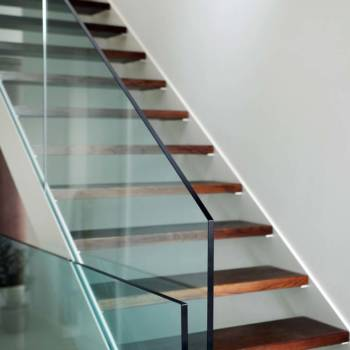 detail of hardened glass balustrade in house with wooden stairs